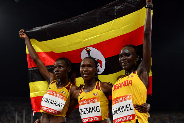 Uganda's Stella Chesang (gold), Mercyline Chelangat (bronze) and Juliet Chekwell celebrate with their flag after the athletics women's 10 000m final during the 2018 Gold Coast Commonwealth Games at the Carrara Stadium on the Gold Coast on April 9, 2018. AFP PHOTO