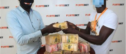 Fortebet's David Ssendagire (L) handing over the money to the winner