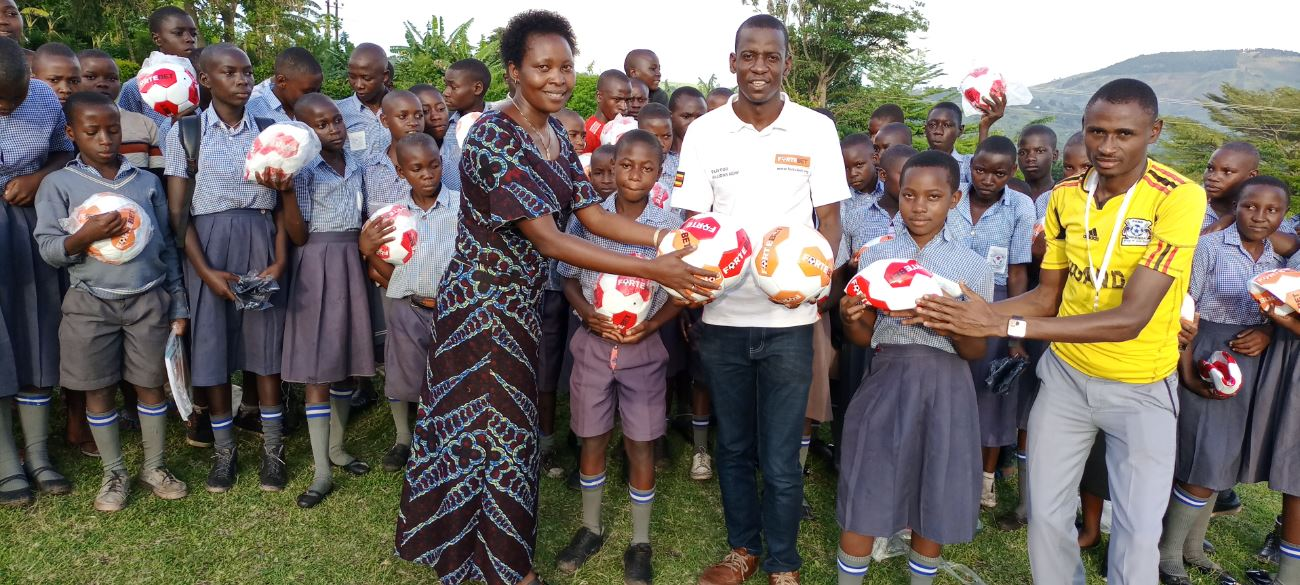 cyclone times Fortebet's John Nanyumba (in white) handing over the balls to the headmistress, Christine Alinaitwe together with gamesmater and pupils
